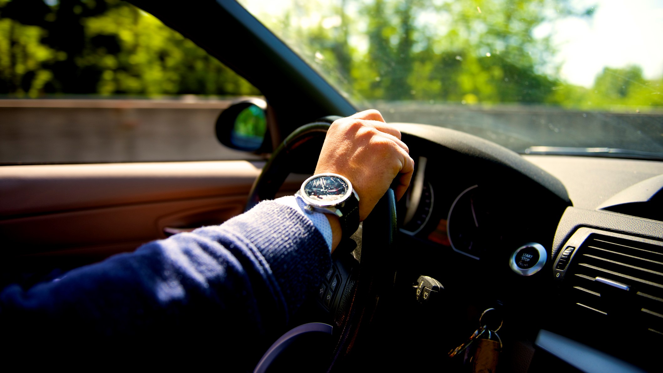 man with watches driving a car