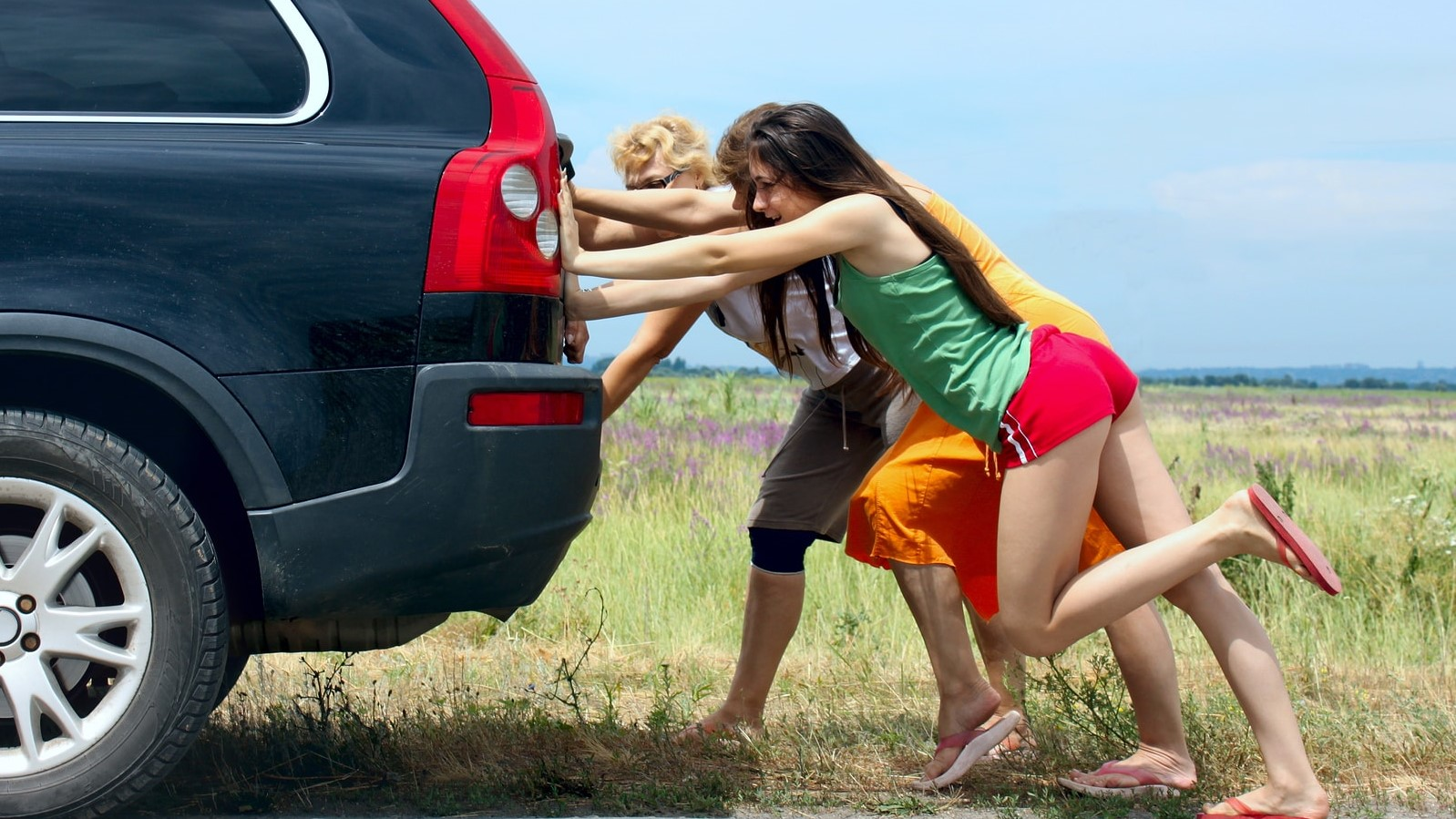 girls trying to jump start a car