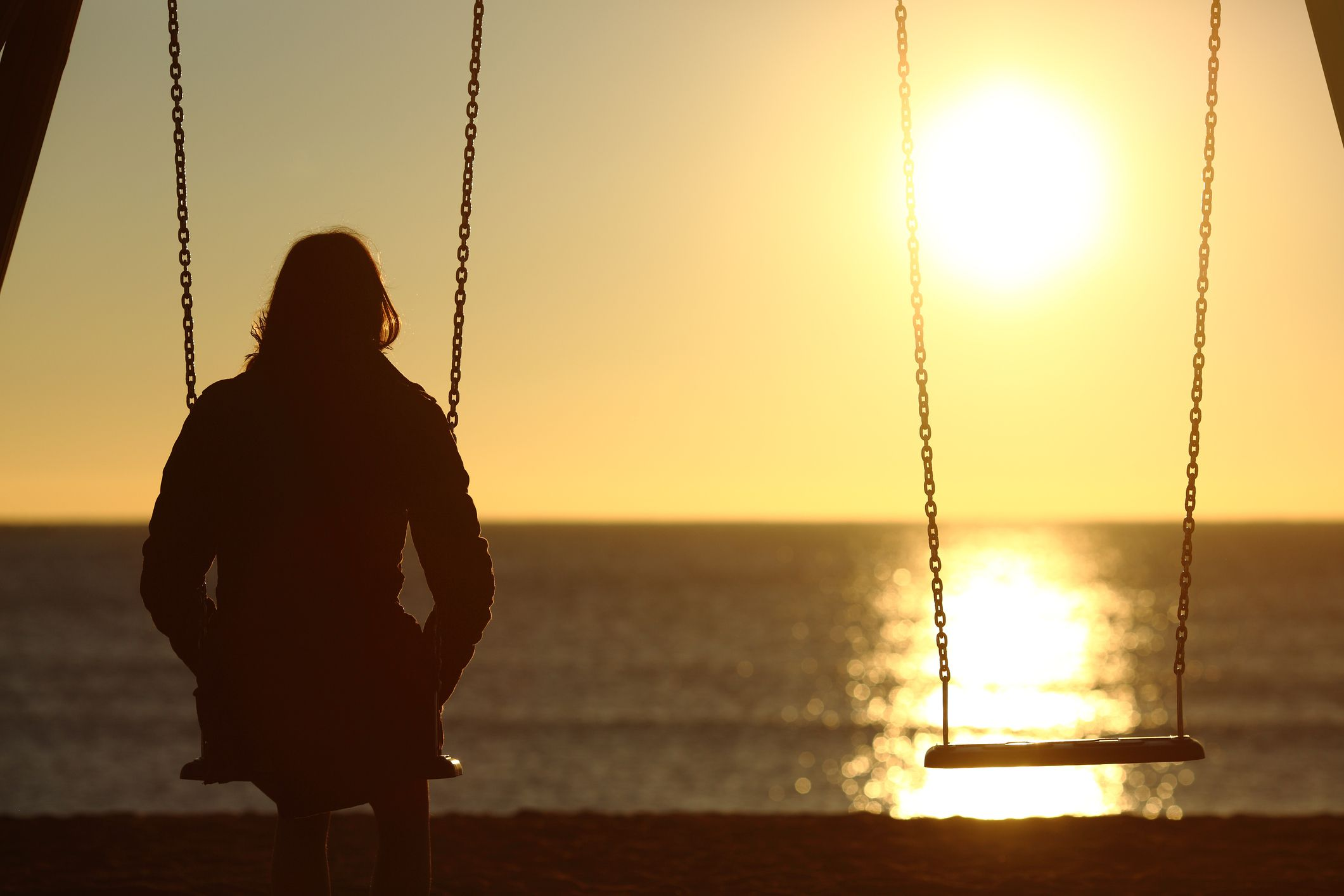 girl sitting staring into the sunset